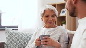 Hijo adulto que trae el café a la madre mayor en casa metrajes