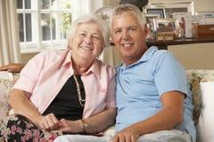 Hijo adulto que visita a la madre mayor que se sienta en Sofa At Home Doing Crochet Imagenes de archivo