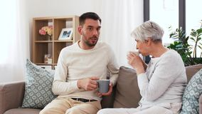 Hijo adulto y café mayor de la bebida de la madre en casa almacen de video
