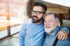 Hijo adulto y padre mayor dentro en casa, mirando hacia fuera E fotografía de archivo