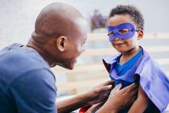 Hijo afroamericano sonriente feliz que es apoyado y ayudado por el padre de apoyo imagenes de archivo