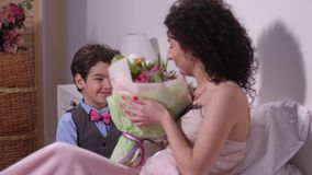 Hijo alegre que da el ramo de tulipanes a la estimada madre almacen de metraje de vídeo