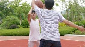 Hijo asiático que hace la falsificación de la bomba al jugar a baloncesto con el padre en jardín en la cámara lenta almacen de metraje de vídeo