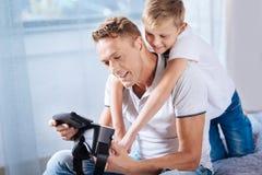Hijo cariñoso que abraza a su padre mientras que él que fija las auriculares de VR Foto de archivo libre de regalías