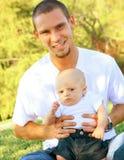 Hijo caucásico joven feliz del padre y del bebé al aire libre Foto de archivo