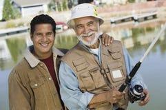 Hijo con el padre que sostiene una caña de pescar imagen de archivo