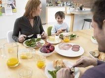 Hijo con los padres que tienen comida en la mesa de comedor Fotografía de archivo libre de regalías