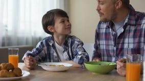 Hijo contento y padre que comen los copos de maíz sabrosos en el desayuno, tradición de la mañana almacen de video
