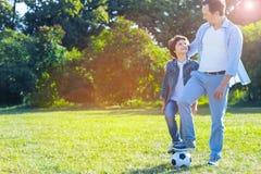 Hijo de abarcamiento del padre cariñoso después de jugar a fútbol Imagenes de archivo
