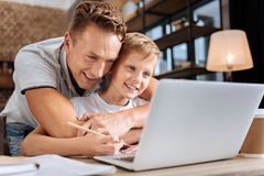 Hijo de abrazo del padre feliz mientras que él que hace la preparación Fotos de archivo
