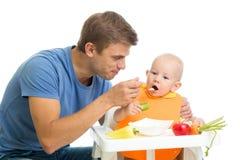 Hijo de alimentación del bebé del padre por la comida sana Foto de archivo libre de regalías