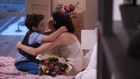 Hijo de amor de la vista lateral que da las flores a la mamá en cama almacen de video