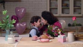 Hijo de amor que da las flores festivas a la mamá feliz almacen de metraje de vídeo