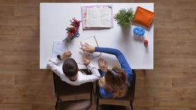 Hijo de ayuda con estudio, mujeres de la madre joven que escriben algo y que muestran al niño, sentándose detrás de la tabla, el  metrajes
