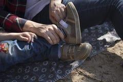 Hijo de ayuda de la madre para llevar los zapatos Una mujer lleva a un niño joven Imagen de archivo