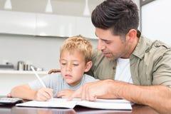 Hijo de ayuda del padre con su preparación de la matemáticas Fotos de archivo