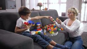 Hijo de ayuda de la madre a construir de bloques del juguete almacen de metraje de vídeo