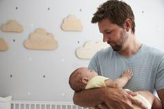 Hijo de Comforting Newborn Baby del padre en cuarto de niños Imagen de archivo libre de regalías