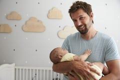 Hijo de Comforting Newborn Baby del padre en cuarto de niños Foto de archivo