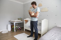 Hijo de Comforting Newborn Baby del padre en cuarto de niños Fotos de archivo libres de regalías