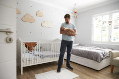 Hijo de Comforting Newborn Baby del padre en cuarto de niños Fotos de archivo