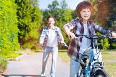 Hijo de enseñanza del padre atento caliente montar la bicicleta Imagen de archivo libre de regalías