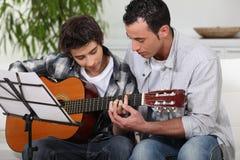 Hijo de enseñanza del padre la guitarra Fotos de archivo