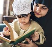 Hijo de enseñanza de la madre para leer Quran imagenes de archivo