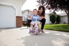 Hijo de enseñanza de la madre para montar la bici Fotografía de archivo