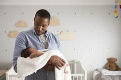 Hijo de Holding Newborn Baby del padre en cuarto de niños Imagen de archivo