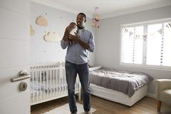 Hijo de Holding Newborn Baby del padre en cuarto de niños Foto de archivo