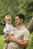 Hijo de la explotación agrícola del padre en parque Fotografía de archivo