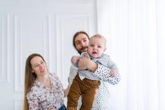 Hijo de la familia, de la mamá, del papá y del bebé en el sitio blanco Foto de archivo libre de regalías