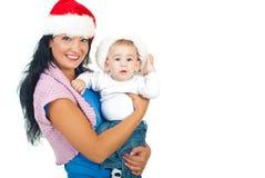 Hijo de la madre y del bebé con los sombreros de Santa Imagen de archivo