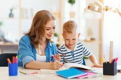 Hijo de la madre y del niño que hace la escritura de la preparación y que lee en casa imágenes de archivo libres de regalías