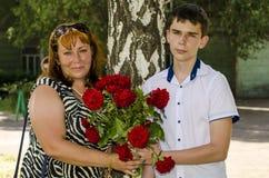 Hijo de la mamá y del adulto con un ramo de flores Imágenes de archivo libres de regalías