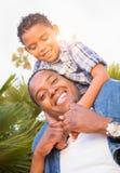 Hijo de la raza mixta y padre Playing Piggyback del afroamericano foto de archivo