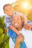 Hijo de la raza mixta y padre Playing Piggyback del afroamericano imagen de archivo libre de regalías