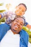 Hijo de la raza mixta y padre Playing Piggyback Out del afroamericano fotos de archivo