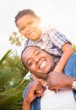 Hijo de la raza mixta y padre Playing Piggyback Out del afroamericano fotografía de archivo