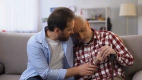 Hijo de mediana edad que conforta al padre de la enfermedad del jubilado terminal, dolor sufridor, cuidado almacen de video