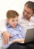 Hijo de observación del padre que trabaja con el ordenador portátil Fotografía de archivo