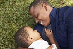 Hijo de Playing With Young del padre en hierba en parque del verano Fotos de archivo