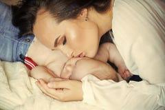 Hijo del bebé del abrazo de la madre dormido en la manta foto de archivo libre de regalías