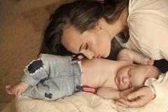 Hijo del bebé del abrazo de la madre dormido en la manta en piso fotografía de archivo