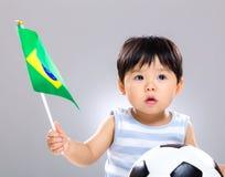 Hijo del bebé que sostiene el balón de fútbol del amd de la bandera Imagen de archivo