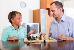 Hijo del hombre y del adolescente que juega a ajedrez Imagenes de archivo