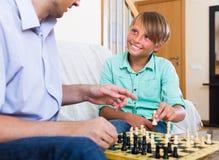 Hijo del hombre y del adolescente que juega a ajedrez Imágenes de archivo libres de regalías