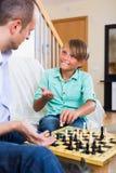 Hijo del hombre y del adolescente que juega a ajedrez Foto de archivo libre de regalías