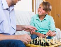 Hijo del hombre y del adolescente que juega a ajedrez Fotografía de archivo